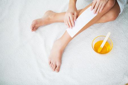 Foto per Waxing. Beautician Waxing Womans Leg In Spa Salon - Immagine Royalty Free