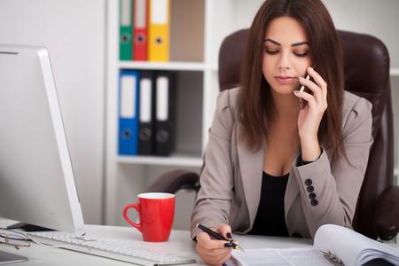 Photo pour Smiling black businesswoman on phone at desk - image libre de droit