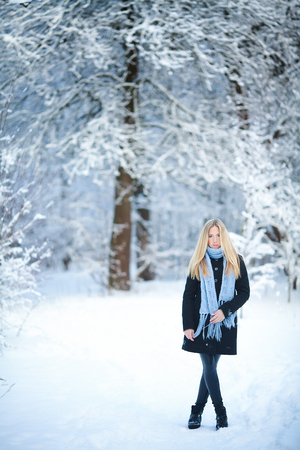 Winter. Young girl walking snowy forest and smiling at the camera. Great mood.
