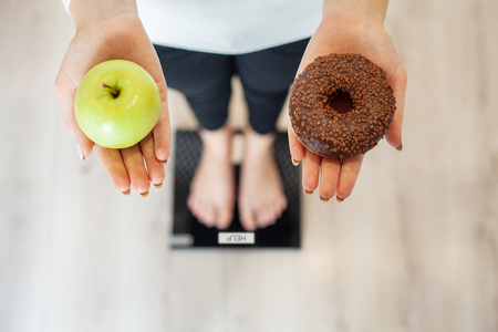 Photo pour Diet. Woman Measuring Body Weight On Weighing Scale Holding Donut and apple. Sweets Are Unhealthy Junk Food. Dieting, Healthy Eating, Lifestyle. Weight Loss. Obesity. Top View - image libre de droit