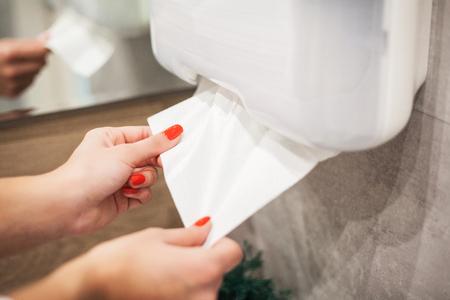 Photo pour Paper towel dispenser. Hand of woman takes paper towel in bathroom - image libre de droit