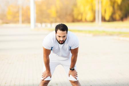 Foto de Fitness. Tired man runner rest after running on city street - Imagen libre de derechos