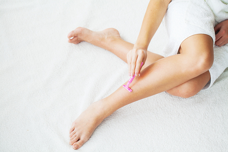 Photo pour Skin Care and Health. Hair Removal. Fit Woman Shaving Her Legs With Razor - image libre de droit