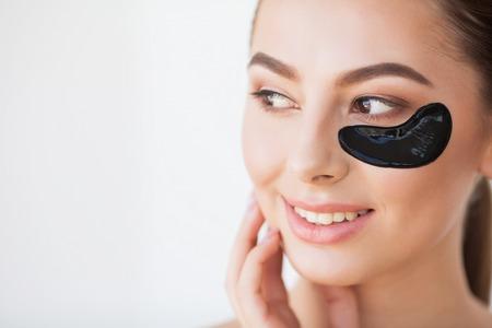 Photo pour Skin Care Mask. Woman With Black Patches - image libre de droit
