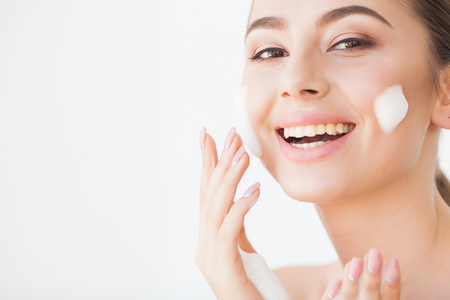Foto de Beauty Face Care. Woman With Cream On Facial Skin - Imagen libre de derechos