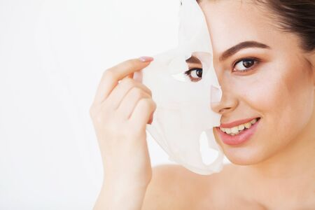 Photo pour Spa and rejuvenation concept. Close up shot of attractive smiling woman removes paper mask from face, satisfied with its effect - image libre de droit