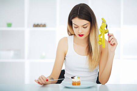 Photo for Diet. Woman hungry girl with yellow measuring tape holds in hand cake cupcake. Weight loss dieting or sweet food and happiness concept. - Royalty Free Image