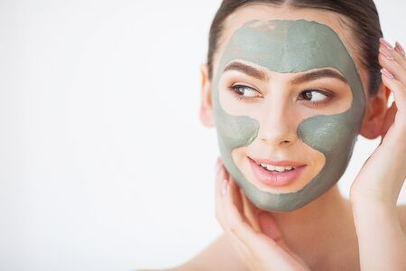 Photo pour Skin Care. Young Woman With Cosmetic Clay Mask Holding Cucumber At Her Bathroom - image libre de droit