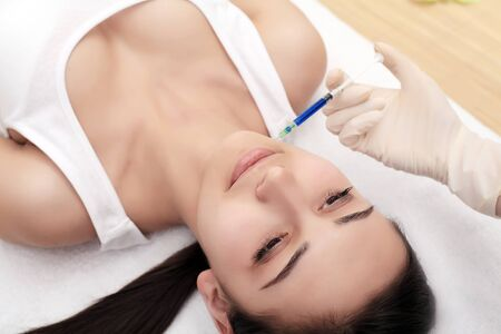 Photo pour Close up of hands of cosmetologist making botox injection in female lips. She is holding syringe. The young beautiful woman is receiving procedure with enjoyment - image libre de droit