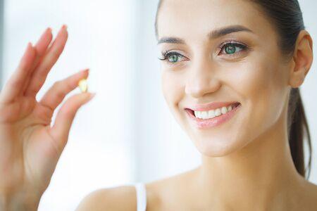 Photo pour Beautiful Woman Taking Pill, Medicine. Vitamins And Supplements - image libre de droit