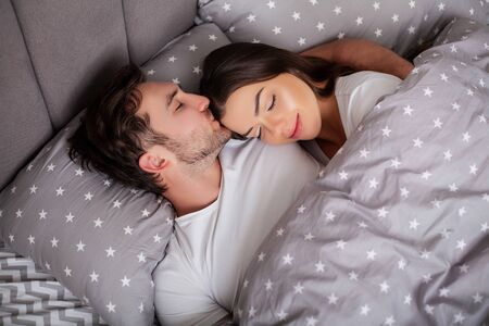 Photo for Happy sensual young couple lying in bed together - Royalty Free Image