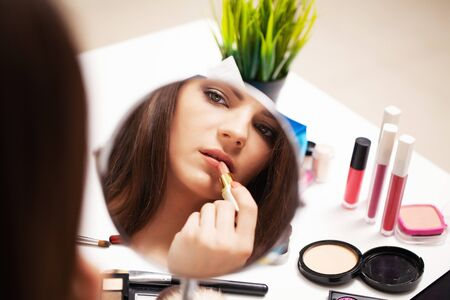 Photo for Pretty girl applies makeup on face at home near mirror - Royalty Free Image