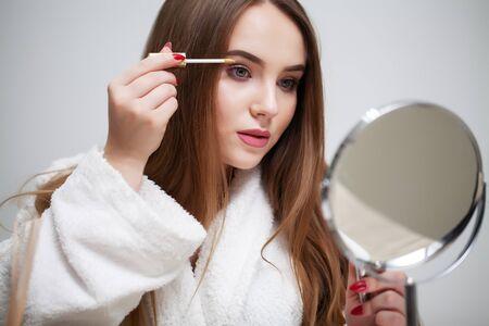 Photo pour Beauty makeup, young woman with beautiful skin holding eyelash brush near eyes - image libre de droit