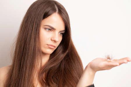Photo pour Very upset young woman has a problem with hair loss - image libre de droit