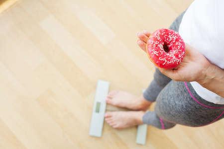 Photo pour Diet concept, woman measures weight on electronic scales while holding calorie donut - image libre de droit