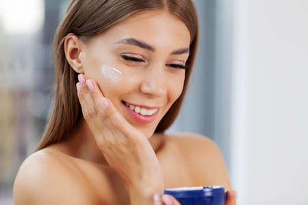 Photo pour Laughing girl applying moisturizing cream on her face. - image libre de droit