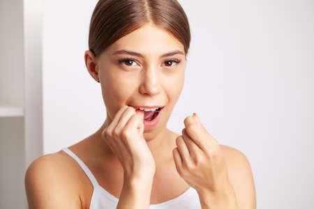 Photo pour Cheerful brunette woman using dental floss in bathroom - image libre de droit