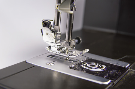 Modern electric sewing machine on a white background. Place for text.