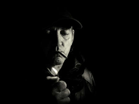 Photo pour A man lights a cigarette with a lighter in the dark. Smoking cigaoretu. Lighter in hand. Man in the dark at night. Portrait of a man. Unshaven. Cap on the head. Black and white photography. - image libre de droit