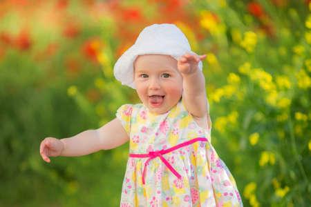 Foto de Portrait of a beautiful little girl having fun in field of red poppy flowers in spring. - Imagen libre de derechos