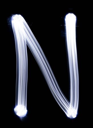 Handwrite letter N, made with light painting technic isolated on black. Light effect font of full alphabet set of upper case letters.