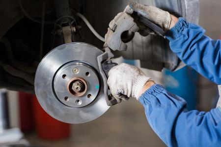 Photo pour Brand new brake disc on car in a garage. Auto mechanic repairing a car. - image libre de droit