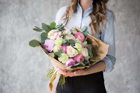 Photo for Florist at work: pretty young woman making fashion modern bouquet of different flowers - Royalty Free Image