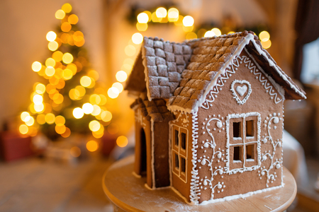 Foto de gingerbread house over defocused lights of Chrismtas decorated fir tree - Imagen libre de derechos