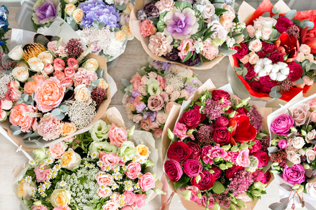 several beautiful bouquet of mixed flowers into a vase on wooden table. top view