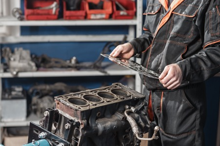 Photo pour The mechanic disassemble block engine vehicle. Engine on a repair stand with piston and connecting rod of automotive technology. Interior of a car repair shop - image libre de droit