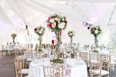 Foto de Interior of a wedding tent decoration ready for guests. Served round banquet table outdoor in marquee decorated flowers and silk. Catering concept. - Imagen libre de derechos