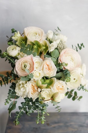 Foto de Wedding bouquet of white roses and buttercup on a wooden table. Lots of greenery, modern asymmetrical disheveled bridal bunch - Imagen libre de derechos