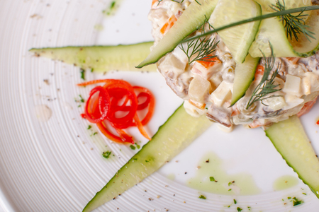 Russian traditional salad Olivier with vegetables and meat. Salad on a white dish on table. restaurant menu