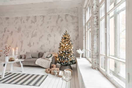 Foto de Light living room with Christmas tree. Comfortable sofa, high large Windows. Light white brick wall. - Imagen libre de derechos