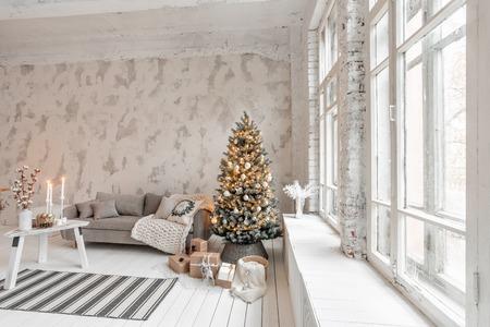 Photo pour Light living room with Christmas tree. Comfortable sofa, high large Windows. Light white brick wall. - image libre de droit