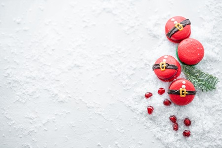 Photo pour Funny cookie in the form red santa belly on gray table sprinkled with snow. Modern european French cuisine. Christmas theme, Merry Christmas card. New year mood. Variety of sweet macaroons. copy space - image libre de droit