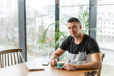 Successful people, businessman in comfortable cafe. Freelancer work on netbook in modern coworking. Young man drinking coffee from a Cup. Programmer at remote job. High large Windows