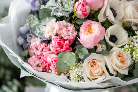 Photo for beautiful fresh cut bouquet of mixed flowers in vase on wooden table. The work of the florist at a flower shop. Delicate Pastel tones color - Royalty Free Image
