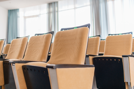 Folding chairs close-up. Big empty modern conference hall in luxury hotel. Audience for Speakers at Business convention and Presentation. Photo for illustration meeting, seminar, conference
