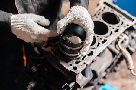Photo pour Close-up Car mechanic holding a new piston for the engine, overhaul.. Engine on a repair stand with piston and connecting rod of automotive technology. Interior of a car repair shop. - image libre de droit