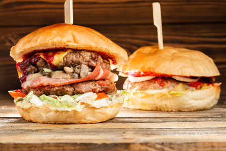 Foto de A big burger with two beef cutlets, cooked on charcoal. Lunch on a wooden background. The concept of fast food and not healthy food - Imagen libre de derechos