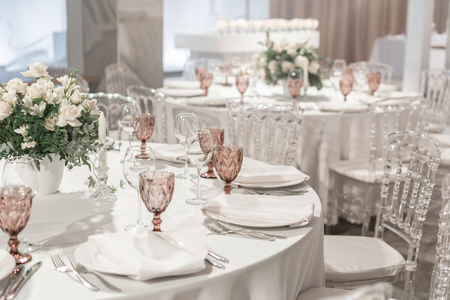 Photo pour Round Banquet table served. Interior of restaurant for wedding dinner, ready for guests. Decorated with floral arrangement. Dishes, wine glasses and napkins. Catering concept. - image libre de droit