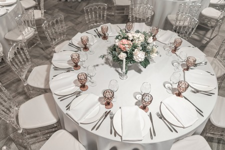 Photo for Interior of restaurant for wedding dinner, ready for guests. Round Banquet table served. Decorated with floral arrangement. Dishes, wine glasses and napkins. Catering concept - Royalty Free Image