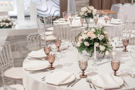 Foto de Flower arrangement in the center of the table. Interior of restaurant for wedding dinner, ready for guests. Round Banquet table served. Catering concept. - Imagen libre de derechos