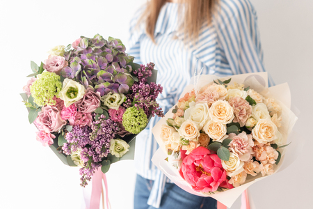 Photo pour Two Beautiful bouquets of mixed flowers in womans hands. the work of the florist at a flower shop. Delicate Pastel color. Fresh cut flower. - image libre de droit