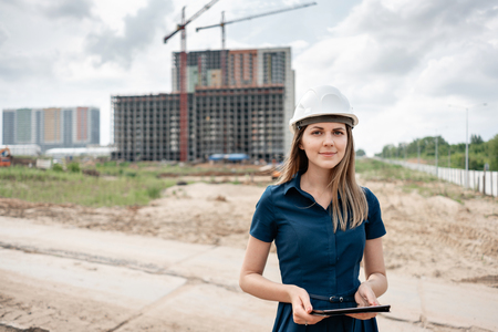 Photo pour Female construction engineer. Architect with a tablet computer at a construction site. Young Woman look in camera, building site place on background. Construction concept - image libre de droit