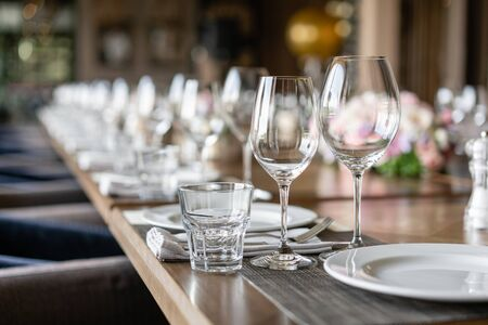 Photo pour Wine glasses in the foreground. Wedding Banquet or gala dinner. The chairs and table for guests, served with cutlery and crockery. - image libre de droit