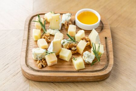 Foto de Cheese plate. Delicious cheese mix with walnuts, honey on wooden table. Tasting dish on a wooden plate. Food for wine. - Imagen libre de derechos