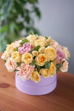 Photo for Florist woman creates flower arrangement in a round box. Beautiful bouquet of mixed flowers. Floral shop concept . Handsome fresh bunch. - Royalty Free Image