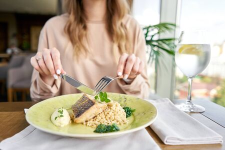 Foto de Roasted Pike perch with spelt and Polish sauce. Lunch in a restaurant, a woman eats delicious and healthy food. Dish decorated with a spinach. Restaurant menu - Imagen libre de derechos